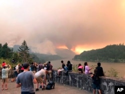 A photo provided by Inciweb shows people at a viewpoint overlooking the Columbia River watching the Eagle Creek wildfire burning in the Columbia River Gorge east of Portland, Oregon, Sept. 4, 2017.