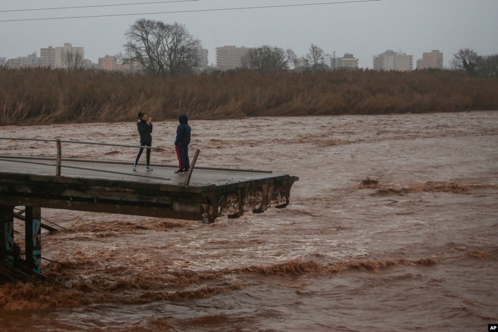 Two people take pictures on top of a collapsed bridge in Malgrat, near Barcelona, Spain.