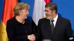 Presiden Mohamed Morsi (kanan) bertemu Kanselir Angela Merkel dalam kunjungan singkat ke Berlin, Jerman hari Rabu (30/1).