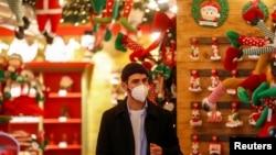 Seorang pria mengenakan masker di dalam sebuah toko ketika pemerintah Italia memaparkan rencana untuk vaksinasi massal Covid-19 dan pembatasan-pembatasan selama masa Natal, di Roma, Italia, 2 Desember 2020. (Foto: Reuters)