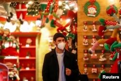 Seorang pria mengenakan masker saat berbelanja di sebuah toko menjelang Natal, di Roma, Italia, 2 Desember 2020. (Foto: Reuters)