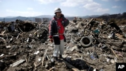 FILE - A firefighter is seen talking on a mobile phone in an earthquake and tsunami devastated area in Rikuzentakata, Iwate Prefecture, northern Japan, April 1, 2011.