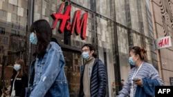 រូបឯកសារ៖ ពលរដ្ឋចិនដើរកាត់ហាងលក់សម្លៀកបំពាក់ H&M ដ៏ល្បីរបស់ក្រុមហ៊ុនស៊ុយអ៊ែត នៅទីក្រុងប៉េកាំង ប្រទេសចិន កាលពីថ្ងៃទី ២៥ ខែមីនា ឆ្នាំ ២០២១។