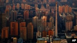 The setting sun illuminates residential buildings in eastern Beijing, as seen from the top of the China World Trade Center Tower 3