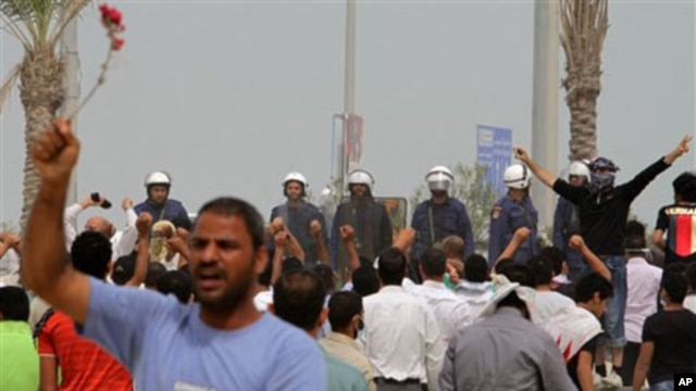 Anti-government protesters chant and wave flowers in front of riot police in Manama, Bahrain, March 13, 2011