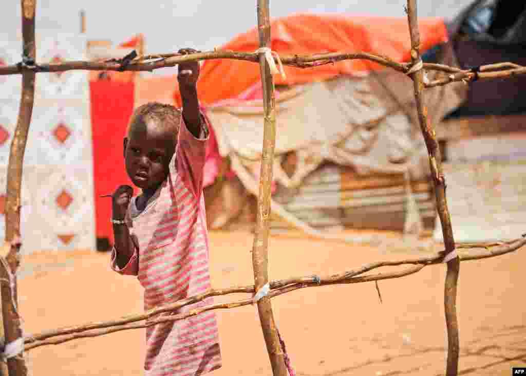 ក្មេងប្រុសជនជាតិសូម៉ាលីម្នាក់ឈរនៅជិតតង់ក្នុងជំរំ Tawakal IDP ទីក្រុង Mogadishu ប្រទេសសូម៉ាលី។