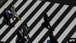 Para pejalan kaki mengenakan masker melintasi jalanan di Tokyo, 8 April 2020.