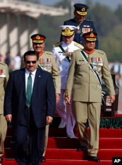 FILE - Pakistan Defense Minister Khurram Dastgir, left, with Army Chief Qamar Javed Bajwa, right, and other officers arrive for a military parade in Islamabad, March 23, 2018.