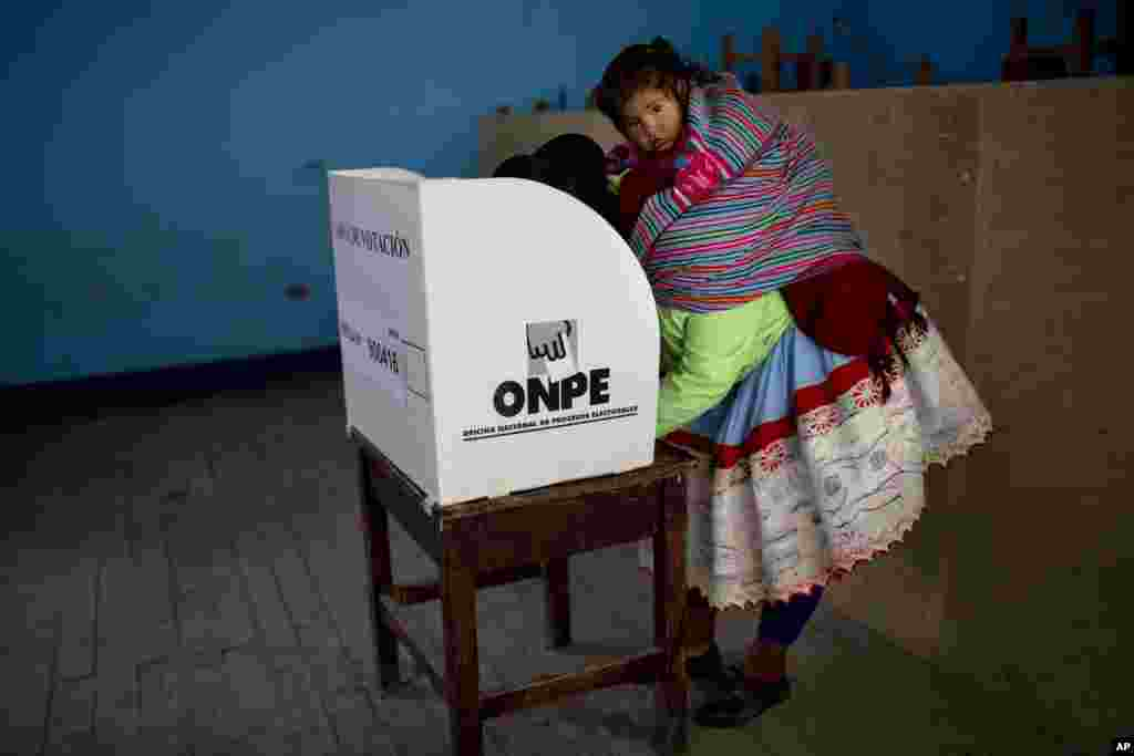 A Quechua indigenous woman casts her vote during general elections in Iquicha, Peru.