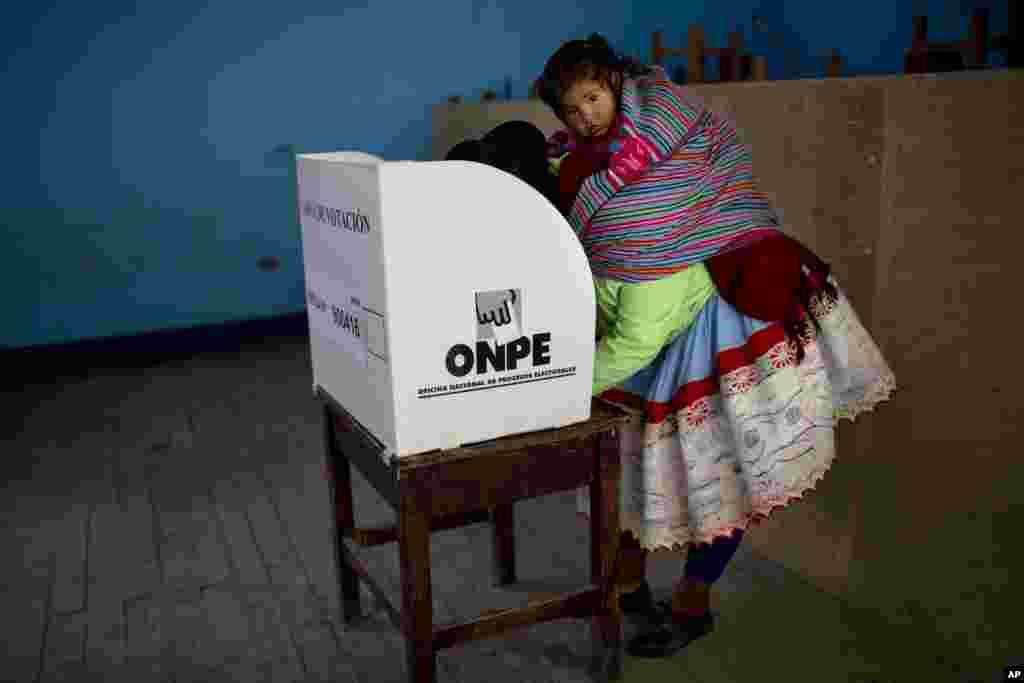 Peru'da sırtında çocuğu ile oy kullanan kadın.
