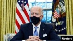 美國總統拜登在白宮橢圓形辦公室簽署行政令。(2021年1月20日)