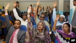 FILE - Somalia lawmakers raise their hands during a confidence vote on Prime Minister Abdiweli Sheikh Ahmed, at the Parliament Building in Mogadishu, Somalia.