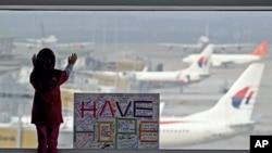 """在马来西亚吉隆坡国际机场,一名女孩透过窗户眺望停机坪,身旁是公众写的""""保持希望""""的标语牌。"""