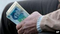 이란의 암달러상이 이란 리알화 뭉치를 들고 있다. 이란에서는 지난 몇 년간 이뤄진 금융제재로 달러화 대비 리알화 가치가 절반 이하로 떨어졌다. (자료사진)