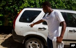 A bystander points to a vehicle, perforated with bullets holes, parked outside the residence of Haitian President Jovenel Moise, in Port-au-Prince, Haiti, Wednesday, July 7, 2021.