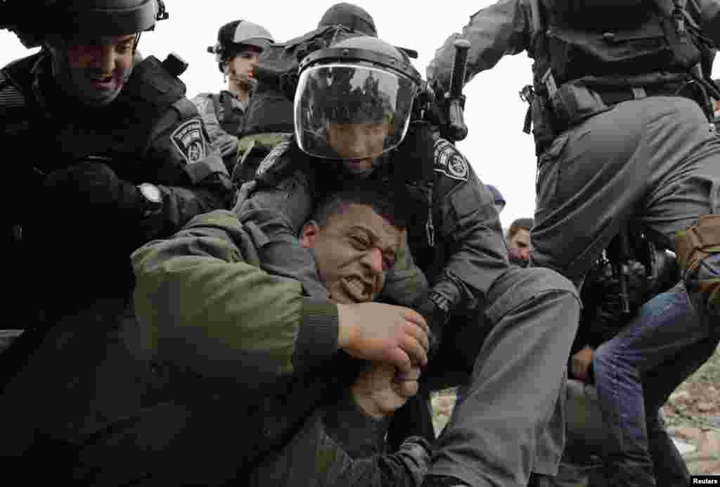 Israeli border policemen detain a Palestinian man as they clear a protest on the land that Palestinians said was confiscated by Israel for Jewish settlements, near the West Bank town of Abu Dis near Jerusalem.
