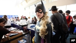 Jessica Chancellor, dressed as Batgirl, waits in line for her credential on Preview Night at Comic-Con International at the San Diego Convention Center, July 20, 2016.
