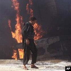 شکار پور میں نذر آتش کیے جانے والے آئل ٹینکروں کے پاس ایک پاکستانی سکیورٹی اہلکار