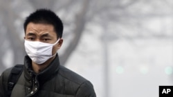 A man wears a mask as he walks to cross a street shrouded by haze in Beijing, China, Jan. 10, 2012.