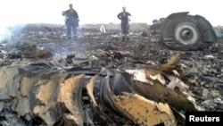 大圖:烏克蘭政府工作人員在飛機出事地點—烏克蘭頓涅茨克附近的一個村莊—了解情況。