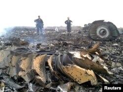 大图:乌克兰政府工作人员在飞机出事地点—乌克兰顿涅茨克附近的一个村庄—了解情况。