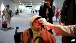 Seorang petugas memeriksa temperatur seorang penumpang setibanya di bandara Soekarno-Hatta, Rabu (22/1). (AP Photo/Tatan Syuflana)