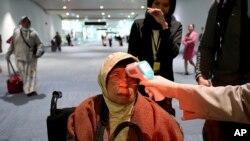 印度尼西亚国际机场工作人员1月22日对入境旅客进行体温检查。