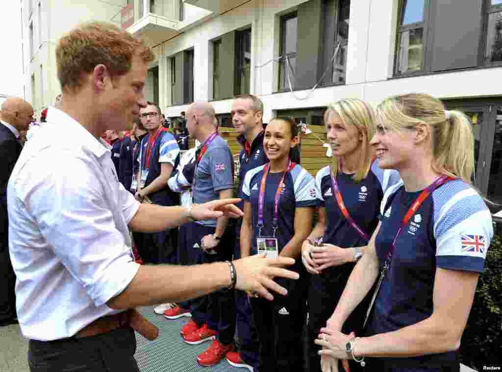 Britain's Prince Harry talks with athletes including British runner Jessica Ennis (3rd R), during a visit to the accommodation for British athletes in the Athletes Village at Olympic Park in Stratford, east London July 31, 2012.