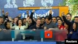 ທ່ານ Mark Zuckerberg ຜູ້ກໍ່ຕັ້ງແລະຫົວໜ້າບໍລິຫານ ຂອງບໍລິສັດ Facebook ບີບກະດິງຕະຫຼາດຮຸ້ນ Nasdaq ທີ່ນະຄອນນິວຢອກ ຈາກສຳນັກງານໃຫຍ່ບໍລິສັດ Facebook ທີ່ລັດຄາລີຟໍເນຍ (18 ພຶດສະພາ 2012)