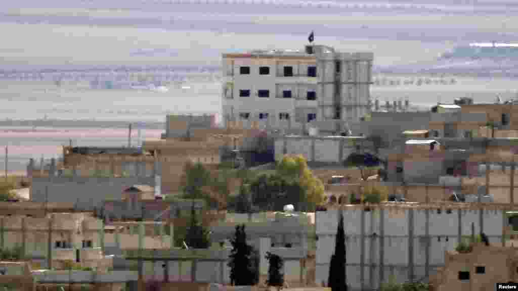 A black flag belonging to the Islamic State is seen in the Syrian town of Kobani, near the Turkish-Syrian border, Oct. 15, 2014.