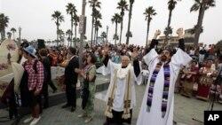 """Para pemimpin kelompok agama yang berbeda-beda bersatu dalam upacara """"Pemberkatan Ombak"""" di Pantai Huntington, California. (Foto: Dok)"""