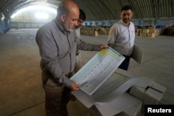 A worker from the Iraqi Independent High Electoral Commission checks voting materials at a warehouse in Najaf, Iraq, April 18, 2018.
