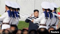 Pemimpin Korea Utara Kim Jong-un memberikan penghormatan kepada para petugas yang berpawai melintasi tribun kehormatan di acara peresmian Taman Makam Pahlawan Korea Utara di Pyongyang (25/7).