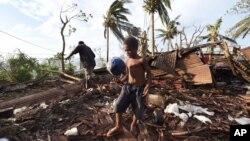 Bé trai Samuel đứng trên đống đổ nát của căn nhà tại Port Vila sau trận bão.