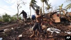 Samuel and his father, Phillip, at back, pick through the debris of their house in Port Vila, Vanuatu in the aftermath of Cyclone Pam Monday, March 16, 2015. (AP Photo/Dave Hunt, Pool)
