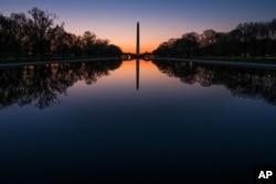 在华盛顿国家大草坪上,黎明之前,华盛顿纪念碑和绿树的影子投射在映影池(2016年4月17日)。