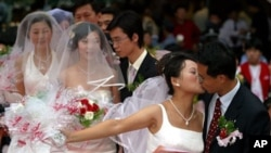 穿着西式婚纱的中国新娘在上海举行的一次集体婚礼上亲吻新郎(资料)