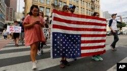 Những người biểu tình cầm lá cờ ngược khi tuần hành chống lại Tổng thống tân cử Donald Trump ở Los Angeles, ngày 12 tháng 11 năm 2016.
