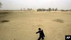 A child walks across a sand dune in Gansu province, China, where desertification threatens for force farmers from their land.
