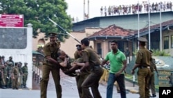 Para narapidana Sri Lanka berteriak-teriak dari atas atap bangunan penjara, saat petugas mengangkat korban yang terluka keluar dari penjara Welikada, Kolombo, Sri Lanka (9/11).