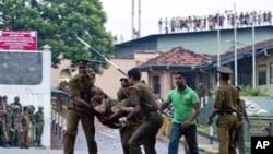 Tại trại tù ở Colombo, Sri Lankan: Các tù nhân la ó trên nóc tòa nhà, trong khi các nhân viên an ninh đang khiêng một đồng nghiệp bị thương, ngày 9/11/2012.