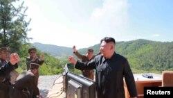 Pemimpin Korea Utara Kim Jong Un bereaksi saat uji coba rudal balistik antar benua Hwasong-14.