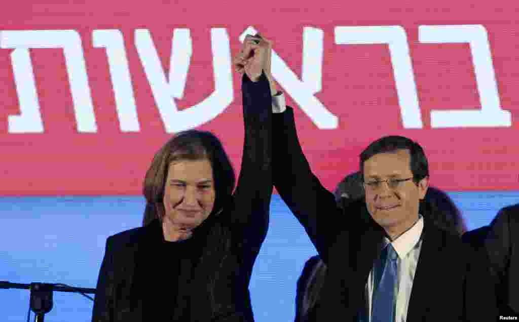 Isaac Herzog and Tzipi Livni, co-leaders of the Zionist Union, raise their arms at party headquarters. Prime Minister Benjamin Netanyahu claimed victory in Israel's election after exit polls showed he had erased his center-left rivals' lead with a hard rightward shift, Tel Aviv, March 18, 2015.