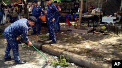 Iraqi security forces clean the scene of a bomb in Kadhimiyah district, Baghdad, Iraq, July 24, 2016.