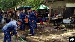 Pasukan keamanan Irak membersihkan lokasi pemboman bunuh diri di distrik Kadhimiyah, Baghdad, Irak hari Minggu (24/7).