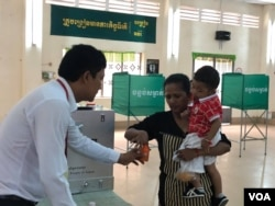 FILE: A Cambodian women inks her finger after casting her ballot at a polling station in Takhmao city, just outside of Cambodia's capital of Phnom Penh, Sunday, July 29, 2018. (Sok Khemara/VOA Khmer)