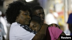 Community members embrace during a vigil at the Triple S Food Mart after the U.S. Justice Department announced it would not charge two police officers in the 2016 fatal shooting of Alton Sterling, in Baton Rouge, La., May 2, 2017. Baton Rouge's police chief said on March 30, 2018, that he had fired the white officer who fatally shot Sterling.