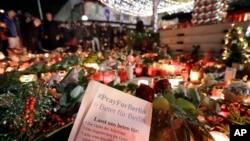 Warga berkumpul di depan lilin-lilin dekat pasar Natal di gereja memorial Kaiser Wilhelm di Berlin, Jerman (21/12), dua hari setelah serangan truk maut. (AP/Michael Sohn)