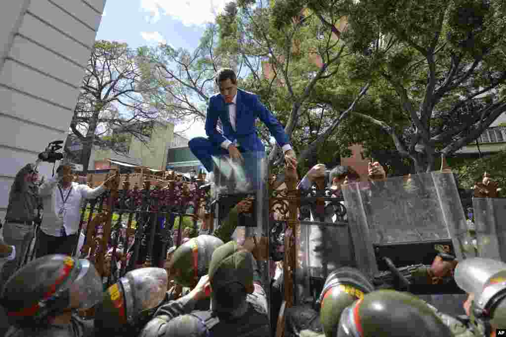 Venezuela's National Assembly President and opposition leader Juan Guaido tries to climb the fence to enter the compound of the Assembly in Caracas, after he and other opposition lawmakers were blocked by police from entering a session to elect new Assembly, Jan. 5, 2020.