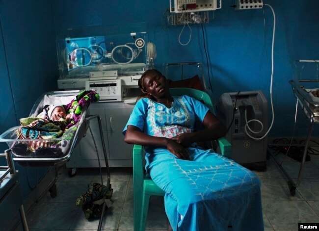 A woman sleeps next to her newborn baby in a nursery in the Juba Teaching Hospital, April 3, 2013. Very few births in South Sudan are assisted by trained midwives.